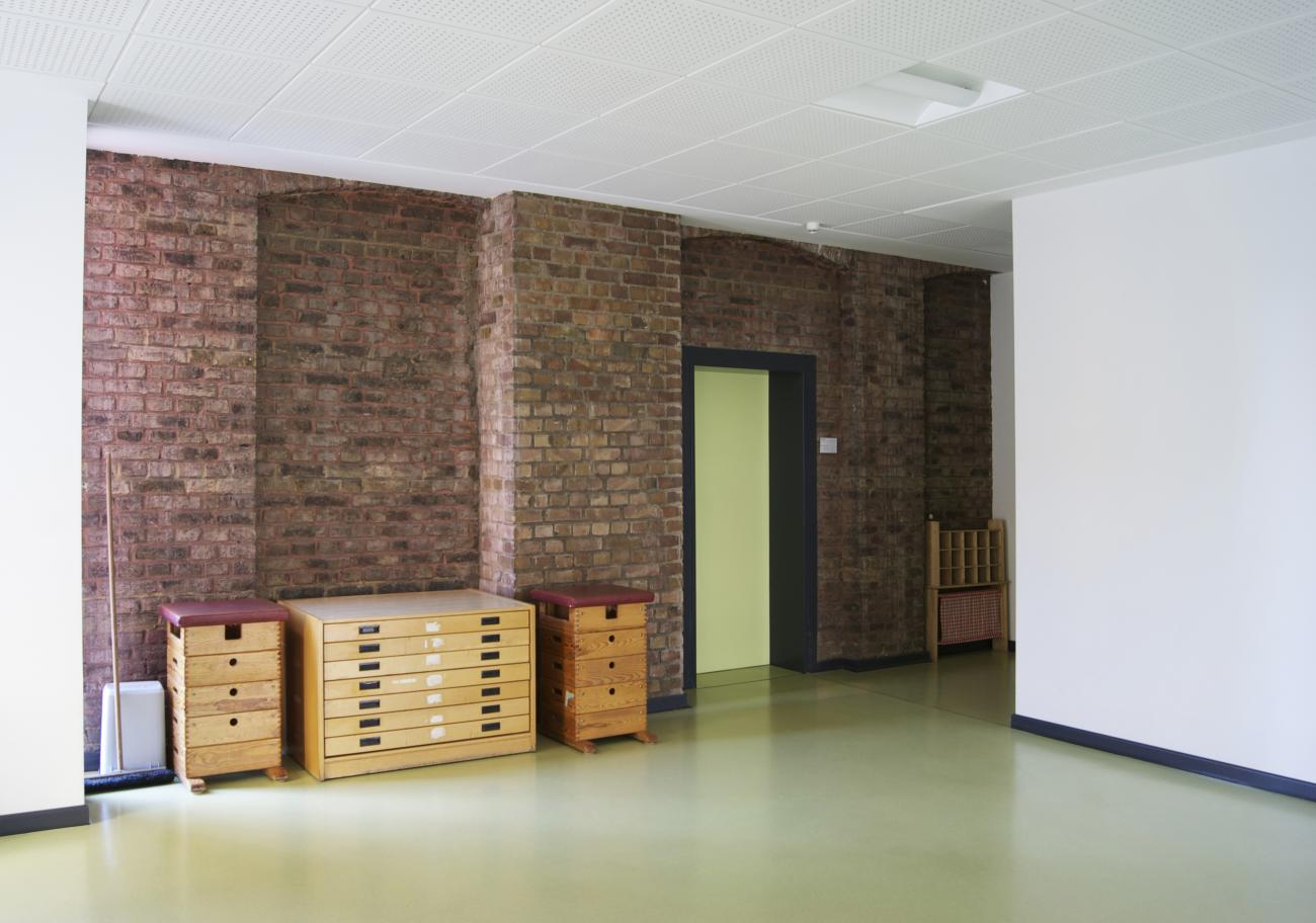 view of an interior wall of brick masonry with door leading to the school building