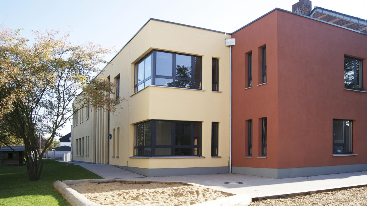 exterior, two-storey kindergarten building with sand play areas